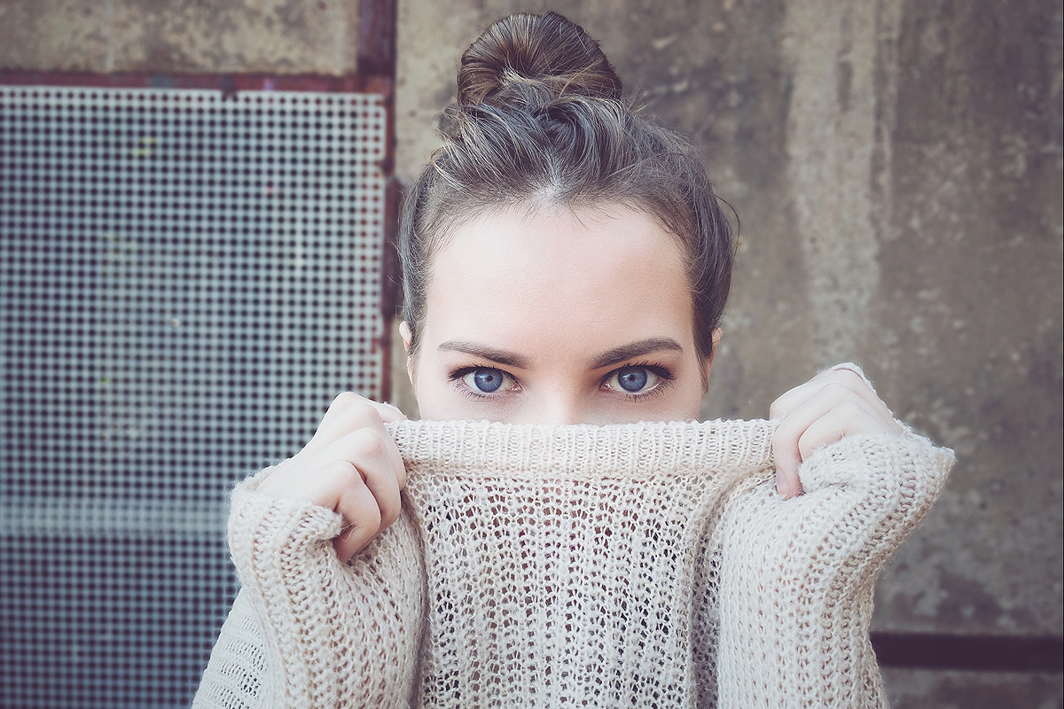 Industrial looking concrete and metal grid background with a white person wearing an off-white knit sweater. They are pulling the sweater up with both hands so that half their face is hidden behind it. Their bright blue eyes are still visible.