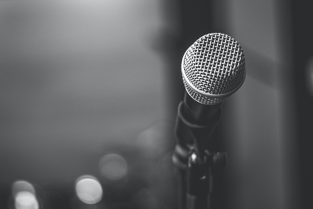 Black and white photograph of a microphone in front of a blurry black background.