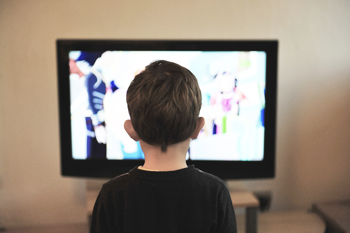 Young white child with short hair, wearing a black sweater, facing away from the camera, standing in front of a TV.