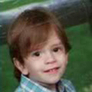 Image depicts Ethan Scott Kirby - a young Caucasian boy with medium long brown hair, his head slightly tilted, smiling into the camera.