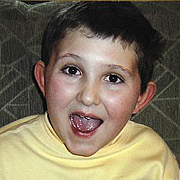 Image depicts Jude Mirra - a young Caucasian boy with short dark hair. He is laughing exitedly into the camera.