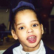 Image depicts Lakesha Victor - a young African American girl with her black hair pulled back into a ponytail held together with a large blue bow, looking intensely at the camera with big eyes and her mouth wide open.