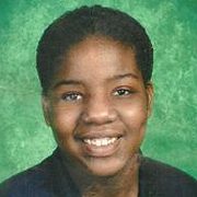 Image depicts Leosha Barnett - an African American teenager with close cropped black hair facing the camera with a wide, bright smile.