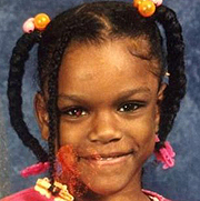 Image depicts Markea Blakely-Berry - a young African American girl with black hair in four chin long twisted braids decorated with colorful hairbands facing the camera smiling.