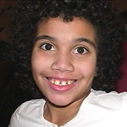 Image depicts Melissa Stoddard - a young girl with shoulder long curly black hair looking directly at the camera with a huge smile.
