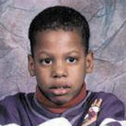 Image depicts Timothy Boss - a young African American boy with close cropped black hair looking intensely the camera with big bright eyes.