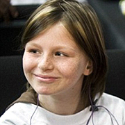 Image depicts Zahra Baker - a young Caucasian girl with shoulder long brown hair with blonde highlights looking towards the left, smiling brightly.