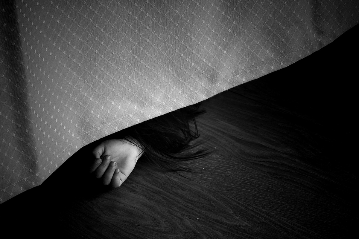 A black and white image of a small child' hand and a part of a head of black hair, laying on the floor, half hidden under a drapery of some kind.