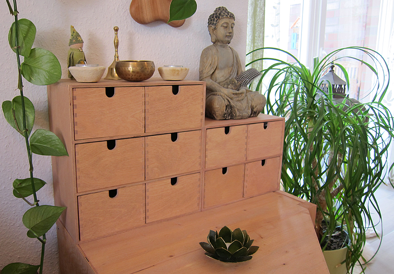 Image shows Autistictics stim toys storage solution: two IKEA mini chests of drawers stained in a beech tone. Placed on top are beige handmade candle holders, a palm sized singing bowl, a small brass bell, and a sitting buddha holding a gemstone and a feather. There are green plants in the background and a window to the right.