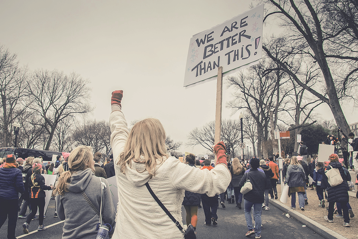"A group of people on the streets, marching, protesting. A person with their back to the camera wearing a white jacket has their left fist raised into the air. In their right hand they carry a sign saying ""We are better than this!"""