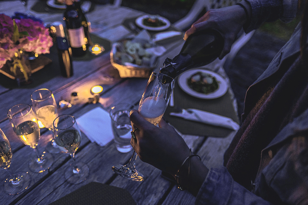 A pair of hands, one holding a glas, the other pouring champagne into it. In the blurry background a table, fully set, ready to sit down and eat at. A lit candle and dark colors suggest it's a night scene.