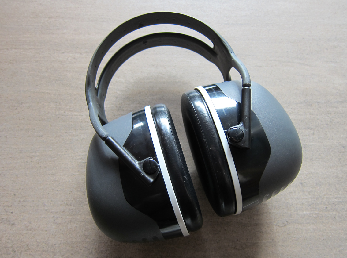 Grey, black, and off-white ear defenders with a plastic twin headband and very thick shells.