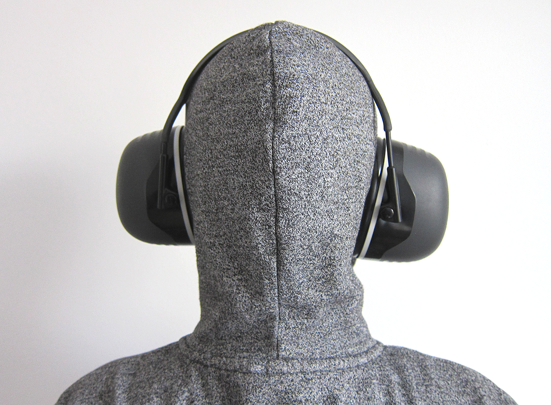 Autistictic from behind, wearing a grey hoodie with the hood up. They are wearing the Peltor X5A ear defenders showing how thick the shells are and how far they stick out which is a lot.