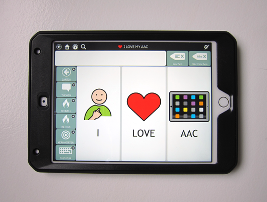 AAC device in black case. The screen shows three large buttons: 'I', 'LOVE', 'AAC' with the corresponding symbols.