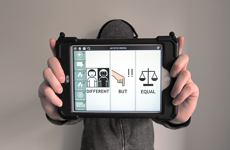 "Autistictic holding their black AAC tablet into the camera. The three large buttons on the screen read ""DIFFERENT"", ""BUT"", ""EQUAL"". Autistictic is wearing a grey hoodie. The AAC tablet is hiding their face."