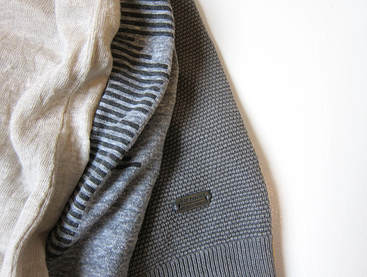 Close-up of three pieces of clothing. The first is beige linen, the second is grey cotton with black pinted on stripes, the third is grey cotton with a square knit texture.