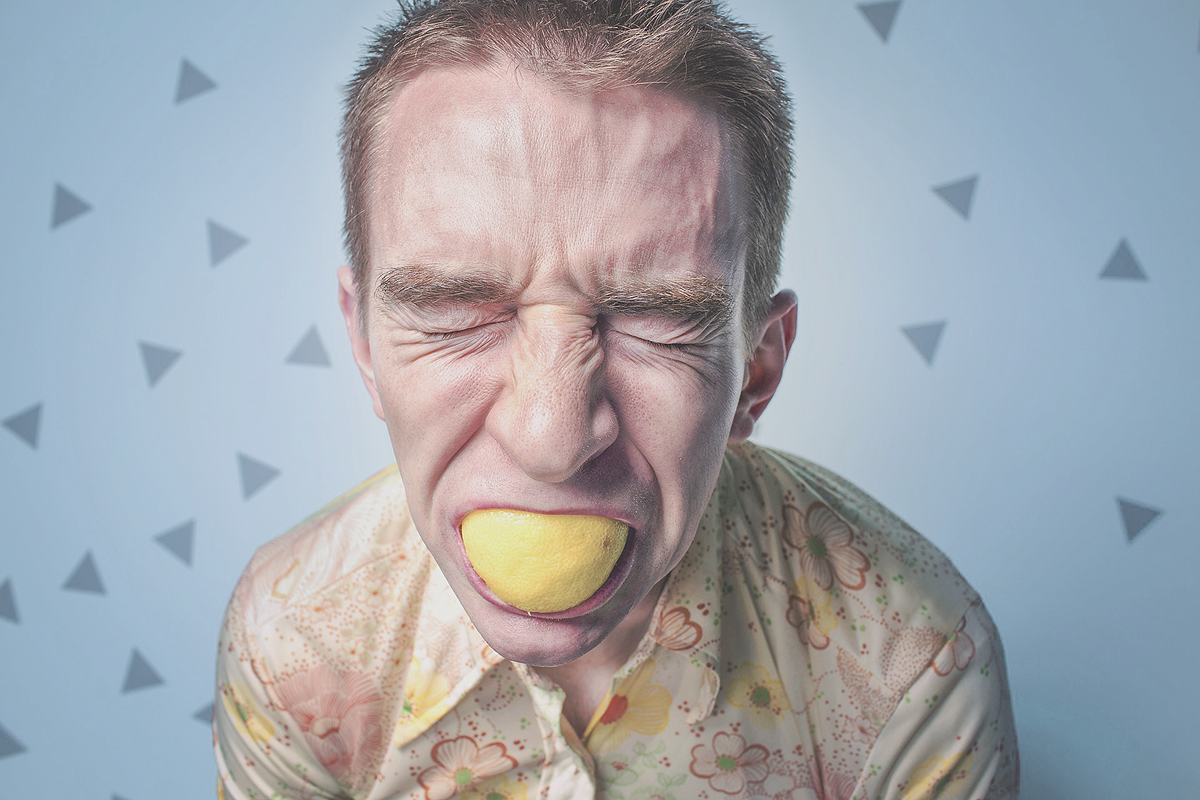 A person with short blonde hair biting into a lemon. Their face is all scrunged up, showing how sour that piece of food is.