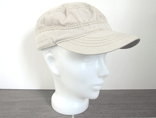 White background, grey floor, white glass head wearing a beige canvas baseball cap.