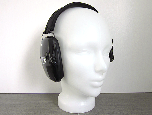White background, grey floor, white glass head wearing slim black ear defenders.