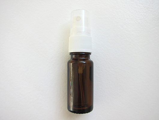 Small spray bottle, brown glass with white closure and transparent lid.