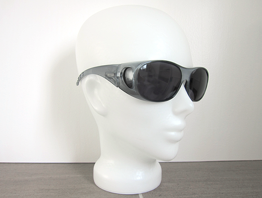 White background, grey floor, white glass head wearing large grey sunglasses with dark grey lenses.