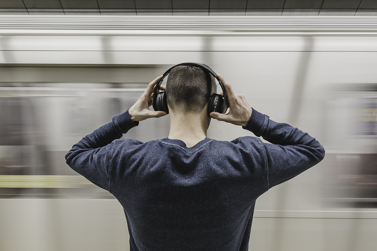 Person standing with their back to the camera. They are putting large over ear headphones on, their hands are still on them.