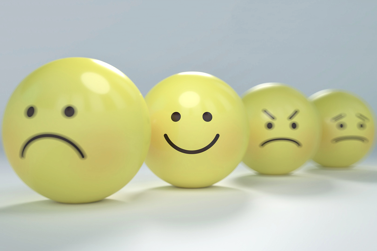 Grey background with four yellow emoticons in a row. The first has a sad face, the second happy, the third angry, the fourth worried.