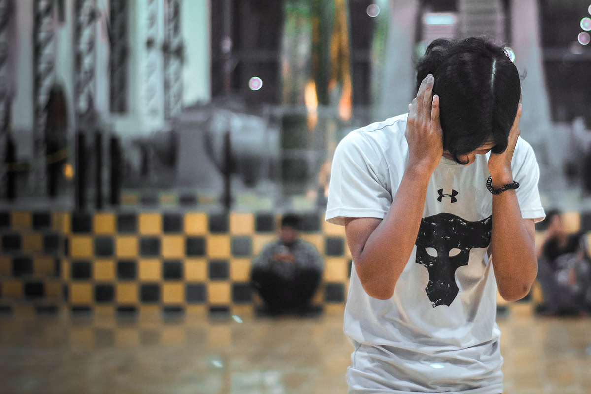 Person covering their ears infront of a busy public area background.