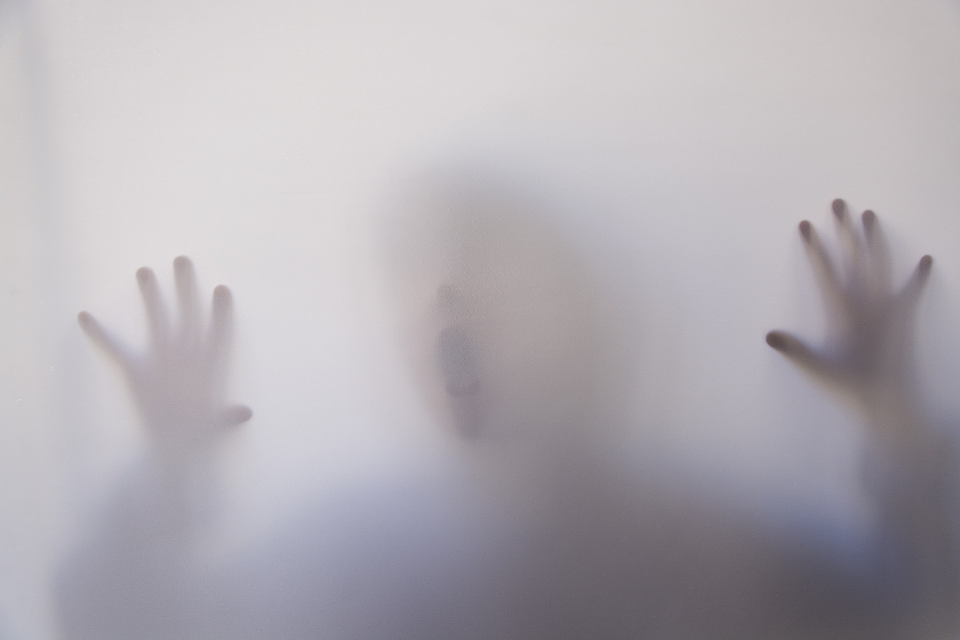 A milky glass with the blurry figure of a child behind it. Both hands are resting against the glass, their face is close to it aswell, their mouth is open as if struggling for air.