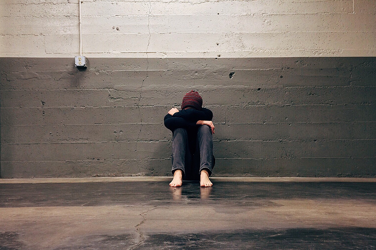 Person sitting with their back to a concrete wall. Their knees drawn towards their body, their arms folded around their knees. Their forehead is resting on their arms, their face invisible. They are barefoot.