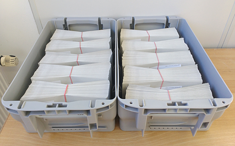 A desk with two grey post boxes on it. Both boxes are filled with hundreds of envelopes bundles into packets with red rubber bands.