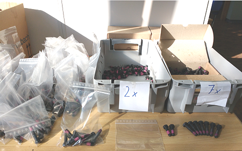 A desk with two grey boxed full of two sizes of screws on it. Left of the boxes are dozens of readily packaged plastic bags filled with screws. In the front an example of a filled bag, an empty plastic bag, two small, and seven large screws.