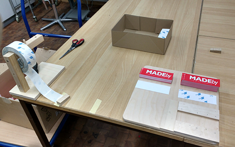 A desk with a box of pre-printed stickers. On the right side there's a contraption attached to the desk that helps a person tear pieces of adhesive tape off a large roll. On the desk there is a wooden board that helps a person attach the adhesive side to the stickers.