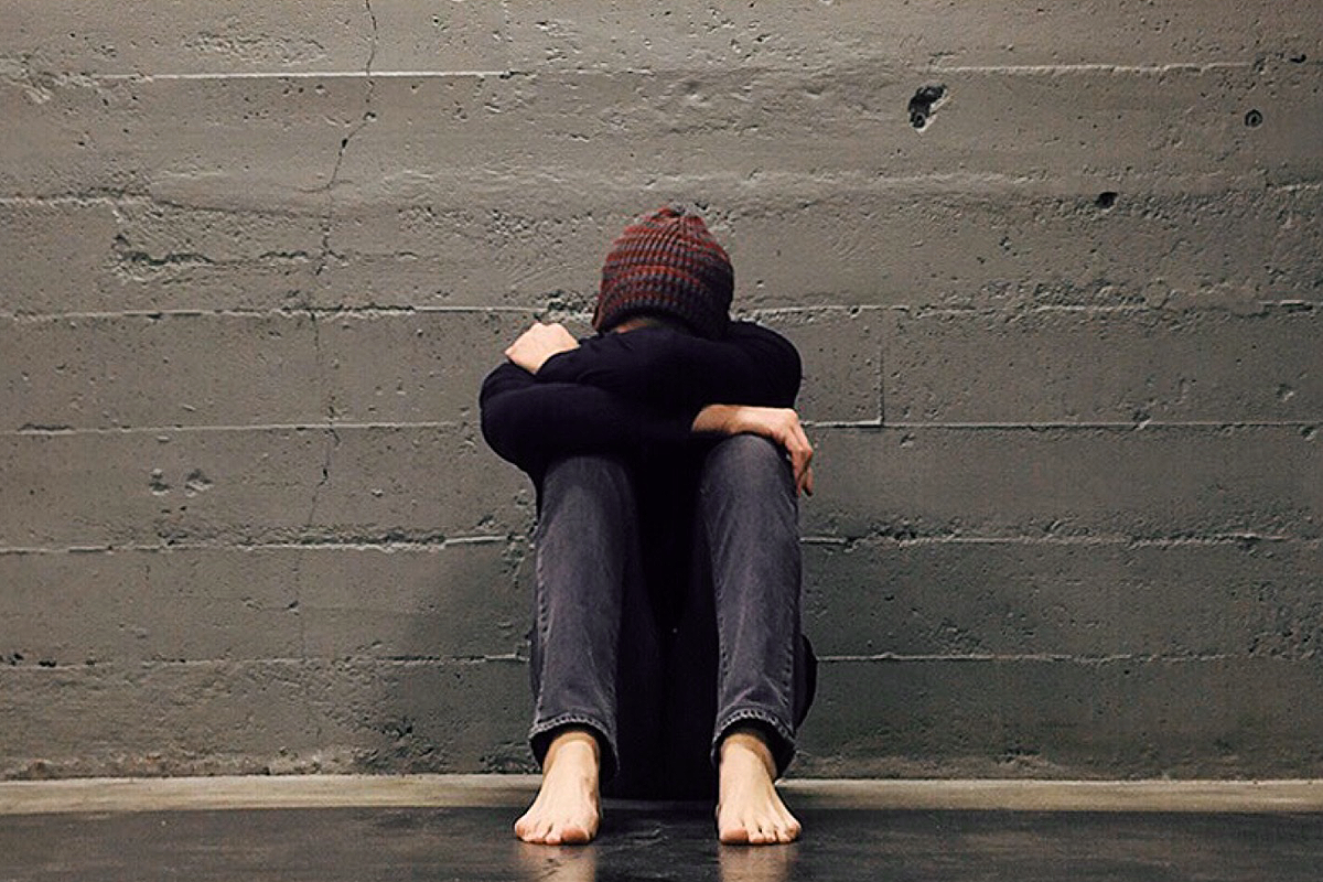 Person sitting in front of a concrete wall, knees drawn to their body, arms wrapped around their knees, head hidden in their arms.