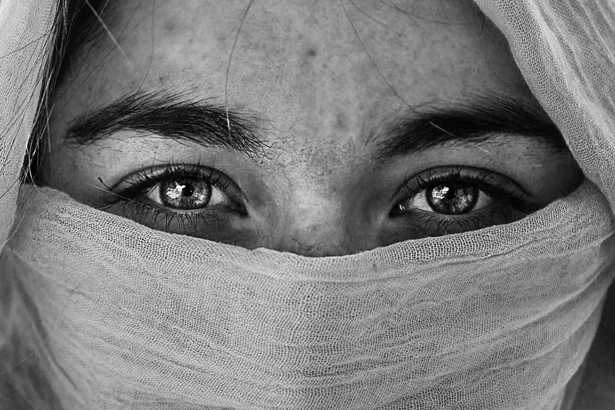 Black and white photograph of a pair of eyes, with thick, bushy, black eyebrows, centered in the frame, staring directly into the camera. The rest of the face is hidden behind a head scarf.