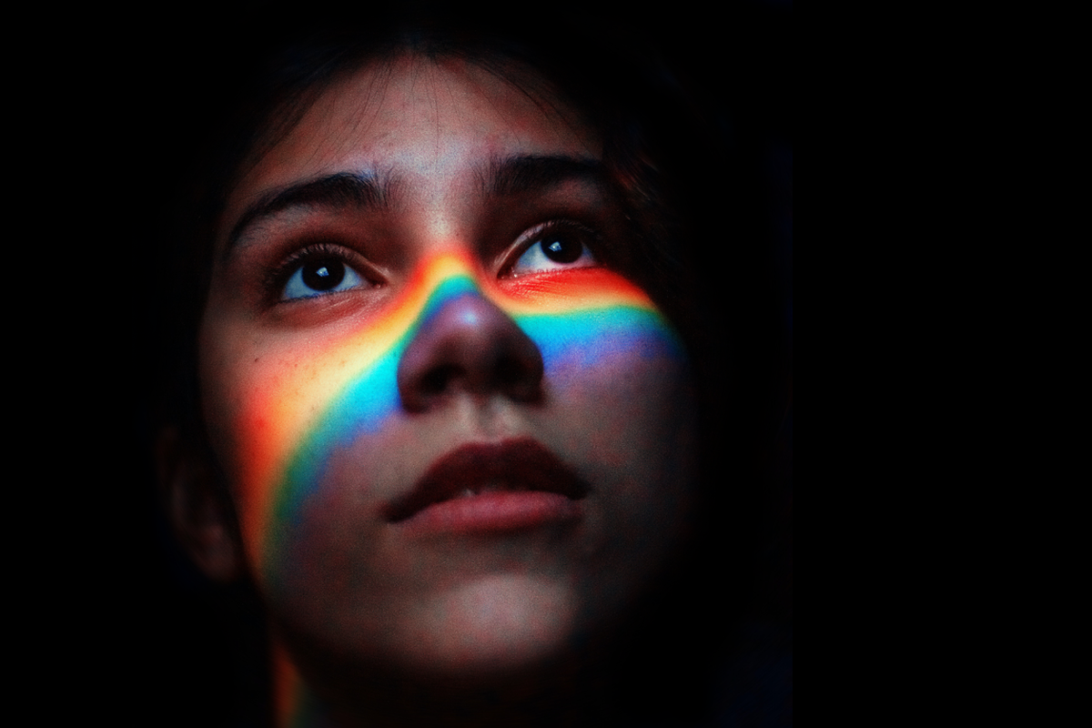 A face with a rainbow over cheek and nose, in front of a deep black background.