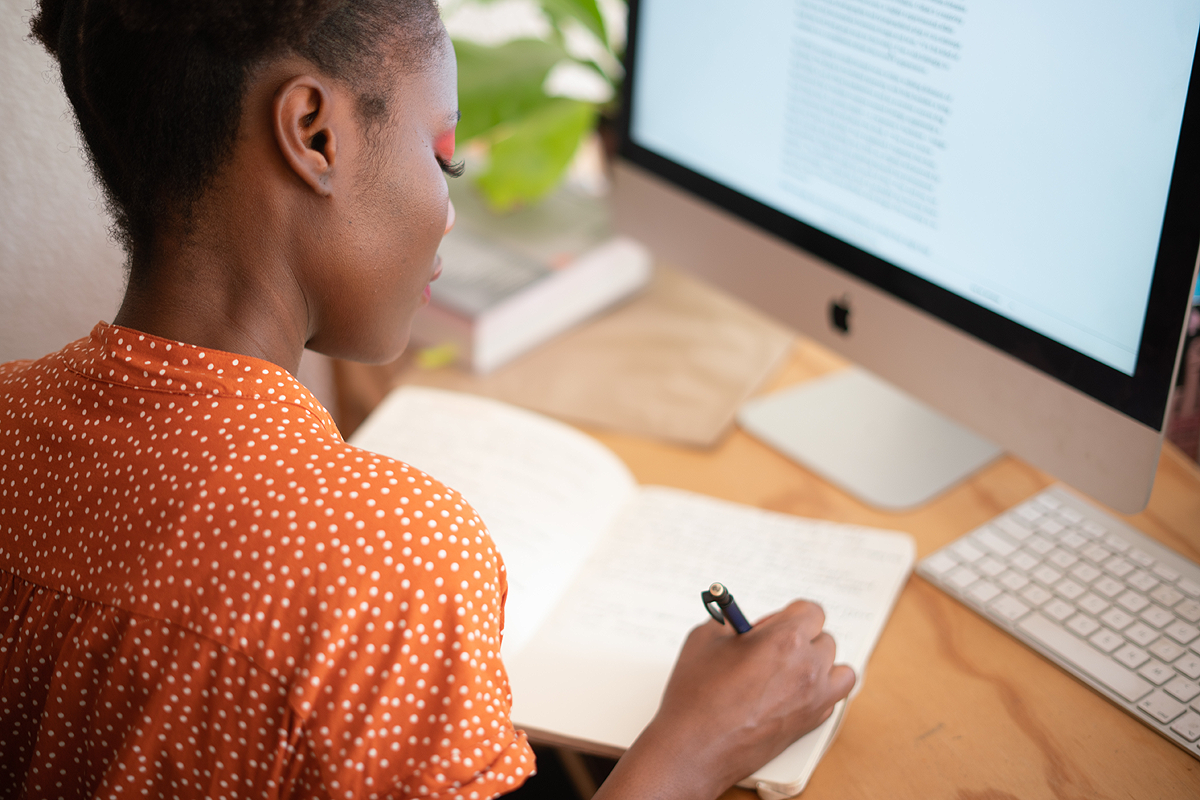 Dark-skinned person wearing an orange patterned shirt sitting at a desk. They have a computer monitor in front of them with a site open and are taking notes in a notebook.