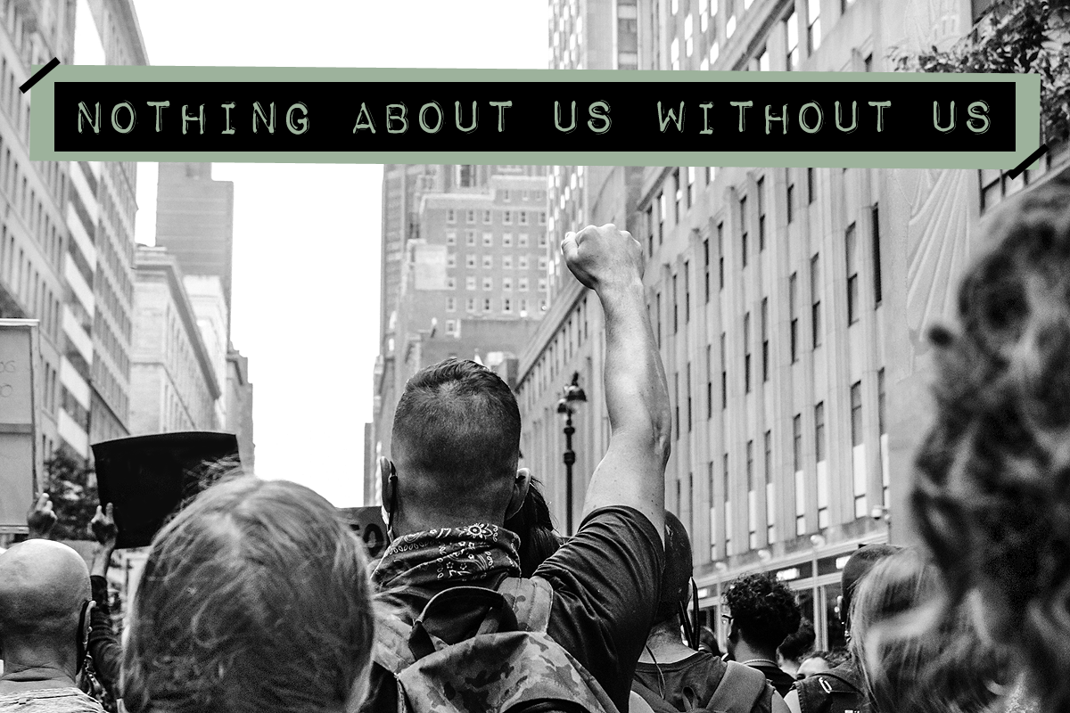 """Black and white image of a protesting crowd marching in the streets. Centered is a protestor raising their fist into the air. The activism slogan """"Nothing about us without us"""" is written in bold, all capital, label style font at the top."""