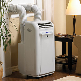 A suitcase-sized portable air conditioning unitin front of a window. Its two tubes are hanging out the window.