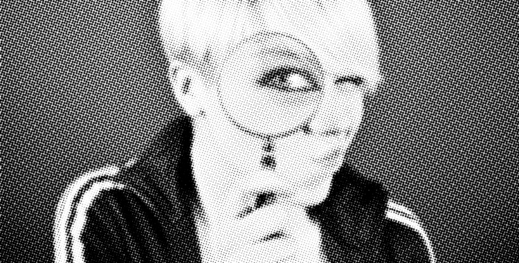 Person with short blonde hair with a magnifying glass infront of their eye. The eye is magnified while the rest of their face is normal sized.