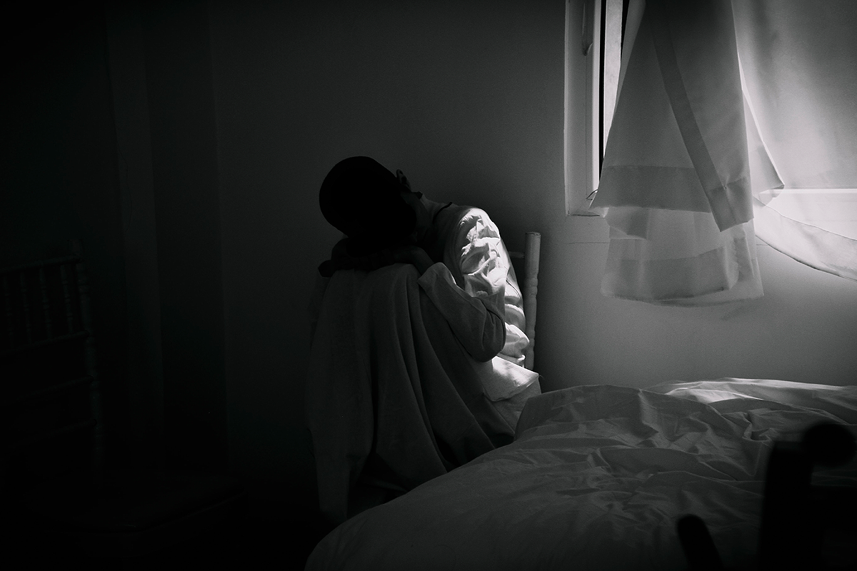Black and white image of a dark, almost completely black room with one window through which light shines. A dark human figure sits on a chair next to the window, feet on the seat of the chair, head resting on their knees. The figure is largely obscured by shadows, only a small part of the left side of their body is lit up by the light that comes through the window. Their face is obscured by shadow.
